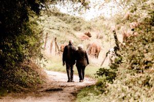 Starý manželský pár se prochází podzimní přírodou
